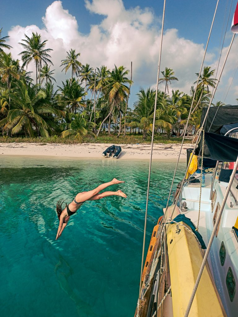 Kalina jumping into turquise Water in of the san blas Islands, Panama